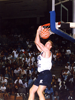 Photograph of a men's basketball player dunking during a game